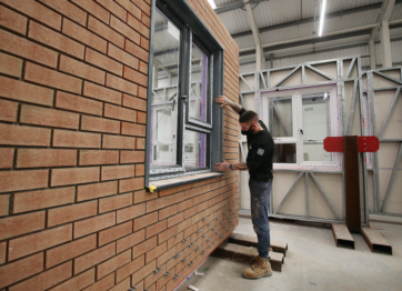 A construction worker building a modular home, working inside a factory